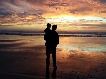 Un adulto y un niño frente a la playa