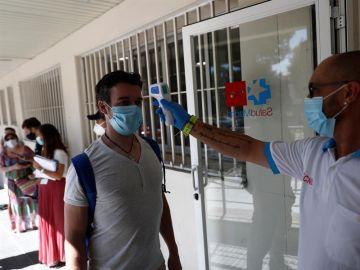 Un sanitario toma la temperatura a una de las personas que esperan su turno para realizarse una prueba de PCR.