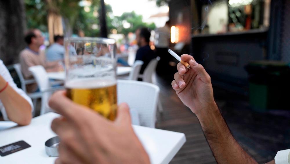 Una persona sostiene un cigarrillo en la terraza de en un bar