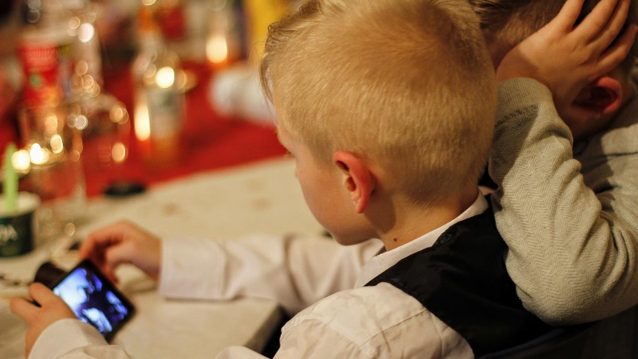 Imagen de archivo de dos niños jugando con un teléfono móvil