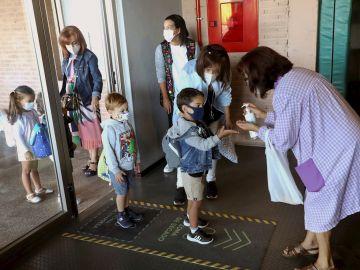 Varios niños entrando al colegio con mascarilla
