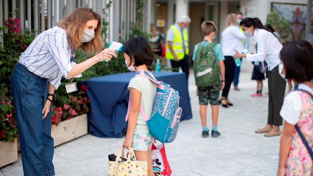 Una trabajadora toma la temperatura a una niña en un colegio de Barcelona