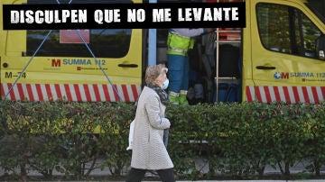 Una mujer pasa ante una ambulancia situada en el barrio de García Noblejas, en el distrito madrileño de Ciudad Lineal