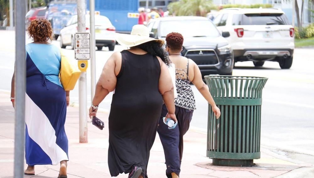 Imagen de tres personas con sobrepeso caminando por la calle