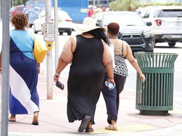 Imagen de tres personas con obesidad caminando por la calle