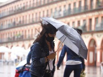 Imagen de una mujer con un paraguas para protegerse de la lluvia