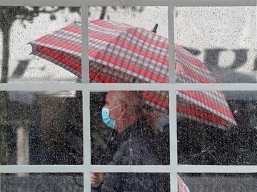 Una persona se protege con un paraguas del agua de la lluvia