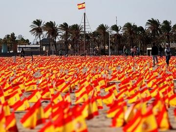 Imagen de las banderas colocadas en una playa de Valencia en homenaje a las víctimas del COVID-19