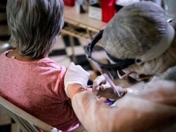 Una enfermera con EPI vacuna a una mujer de la gripe