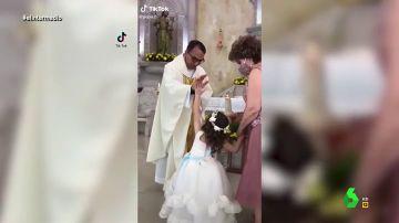 La reacción viral de una niña chocando los cinco a un cura que la intenta bendecir en plena misa