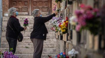 Varias mujeres colocan flores en una tumba del cementerio de Alcalá