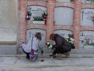 Dos mujeres dejan flores en un cementerio