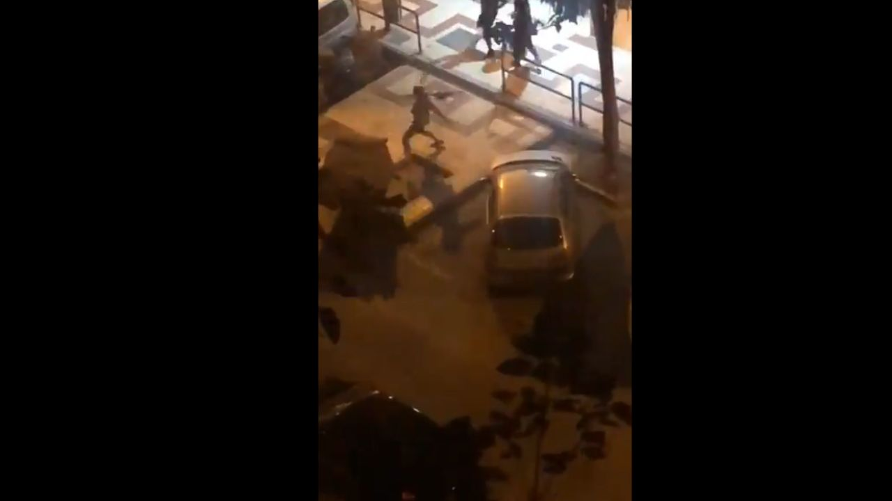 Un violento tira un contenedor durante los disturbios en Málaga