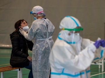 Imagen de una sanitaria haciendo una PCR a una mujer