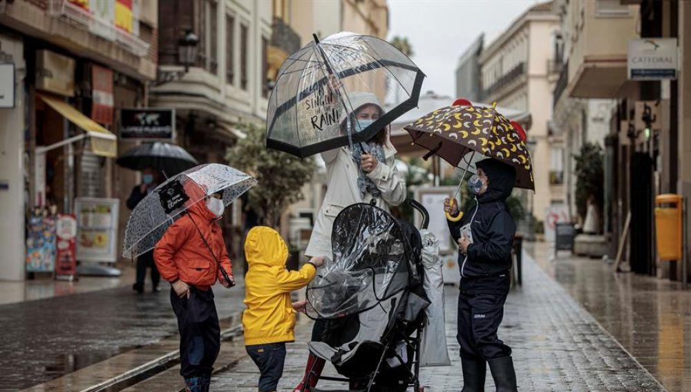 Una mujer con tres menores se protegen de la lluvia con paraguas y chubasqueros en Valencia.