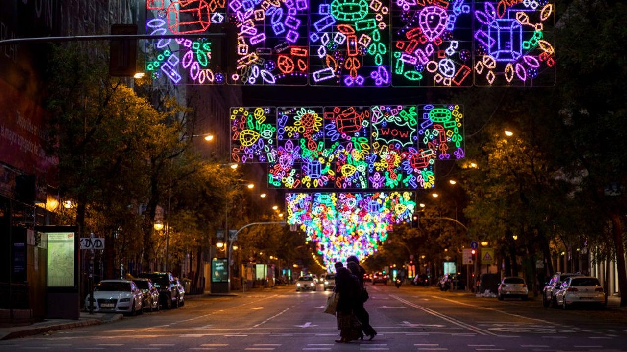 Varias personas cruzan por un paso de cebra de la calle Goya, en Madrid, bajo una colorida iluminación de Navidad