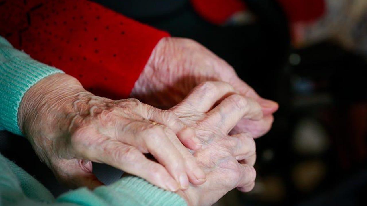 Una pareja de ancianos se da la mano