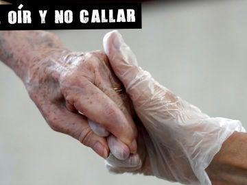 Una sanitaria sostiene la mano de una anciana
