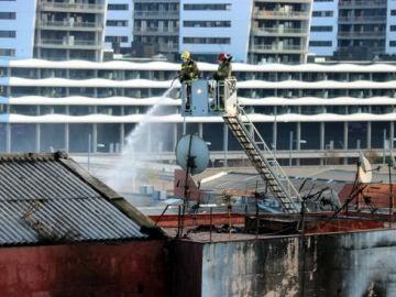 Bomberos en labores de extinción en la nave incendiada en Badalona.