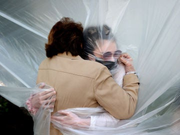 Una mujer abraza a su abuela durante la pandemia de coronavirus