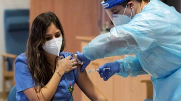 Imagen de una sanitaria mientras le inyectan la vacuna