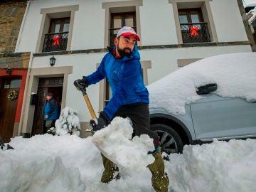 Vecinos de la localidad asturiana de Pajares retiran la nieve de los caminos, este sábado
