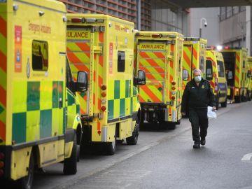 Un sanitario camina junto a una hilera de ambulancias en el Royal London Hospital
