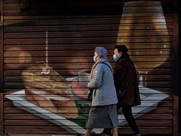 Personas caminan frente a un establecimiento cerrado