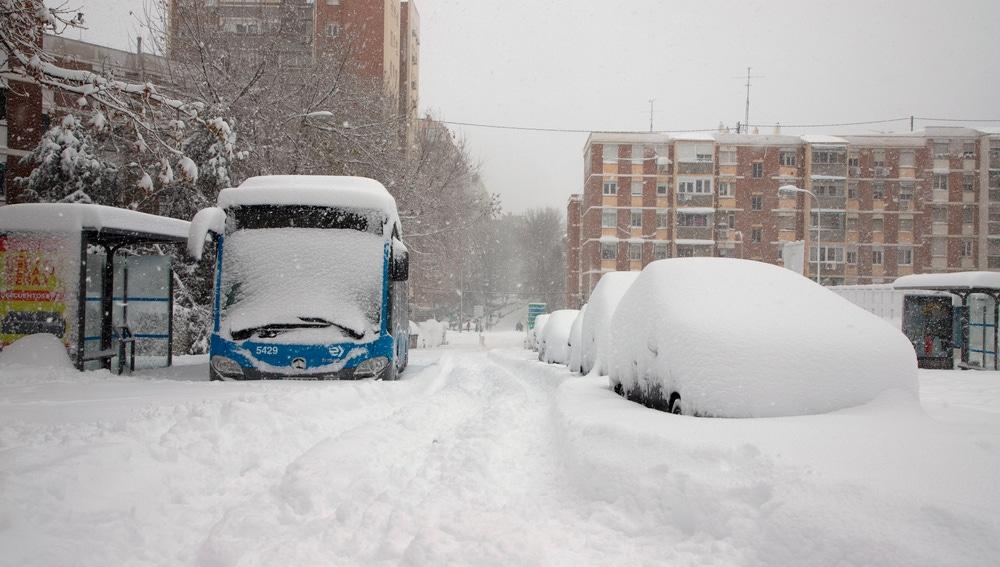 Autobuses y coches sepultados bajo la nieve en Madrid