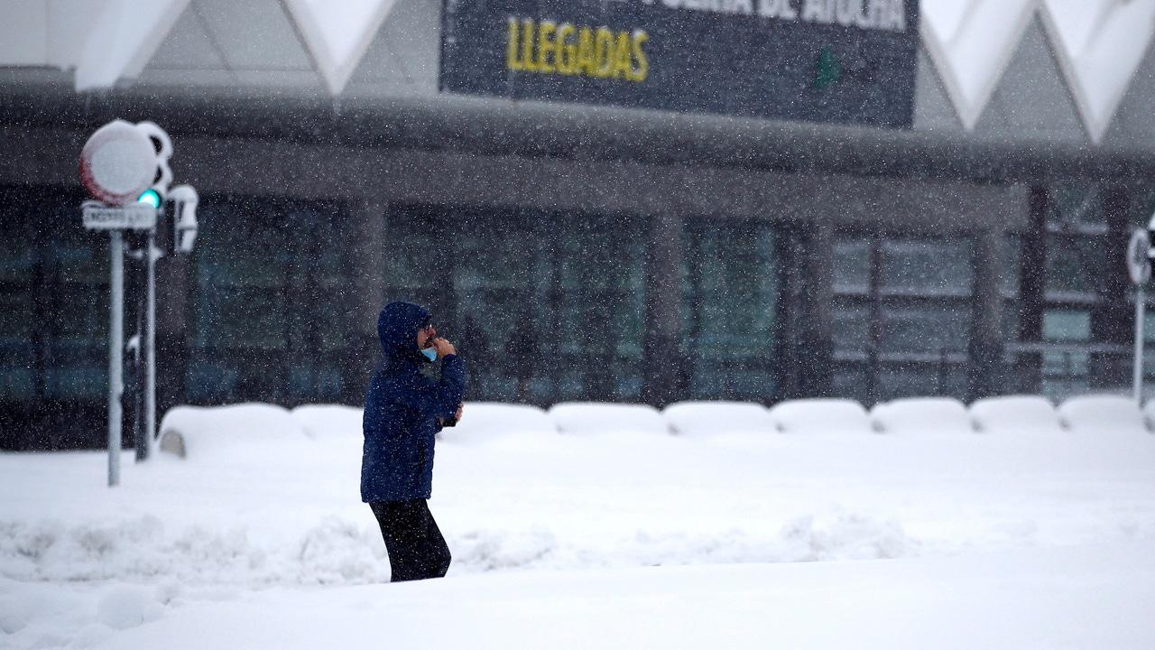 Un hombre espera en la estación de Atocha bajo la nieve