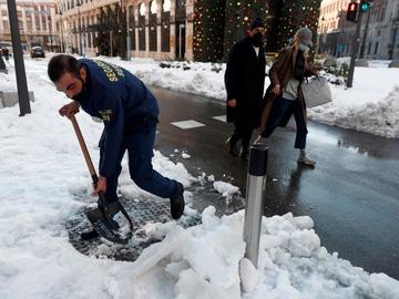 Un operario retira nieve de la acera este lunes en Madrid