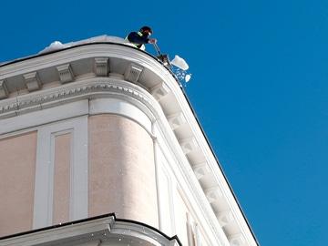 Un operario retira nieve del techo de una vivienda este lunes en Madrid