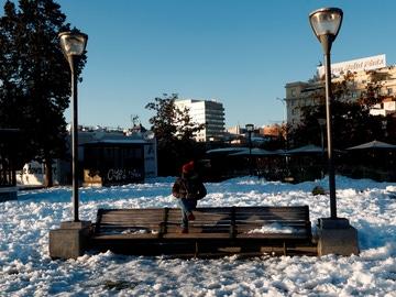 Un hombre sentado en un banco, rodeado de nieve este lunes en la plaza de Colón de Madrid