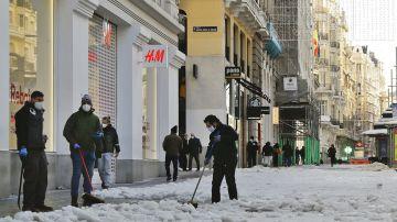 Varias personas limpian la nieve y el hielo de las aceras en la Gran Vía de Madrid