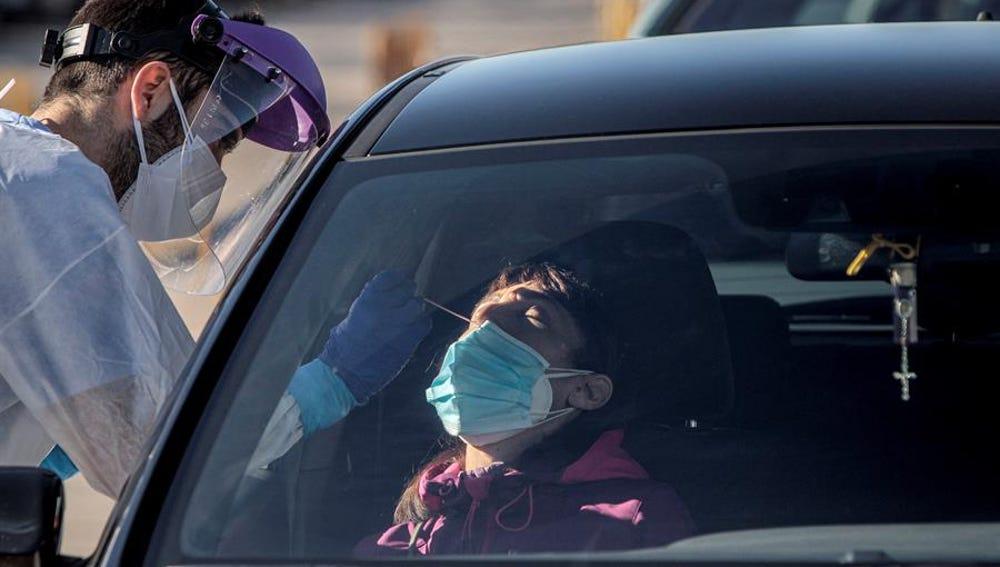 Un sanitario realiza test para detectar la covid-19 a pacientes en sus vehículos frente al hospital de campaña de La Fe de Valencia.