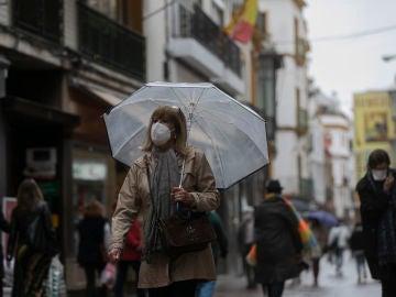Una mujer bajo su paraguas en Sevilla