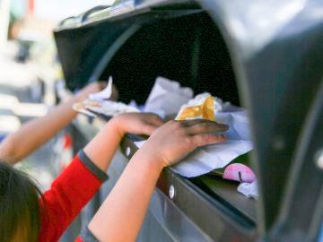 Un grupo de niños y niñas, reciclando un contenedor azul de papel y cartón