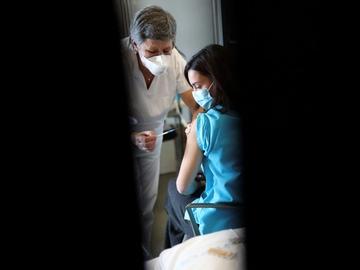 Una sanitaria es vacunada contra la COVID-19 en Barcelona