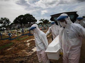 Trabajadores entierran a una persona fallecida por coronavirus en el cementerio público Nossa Senhora Aparecida en Manaos, Amazonas.