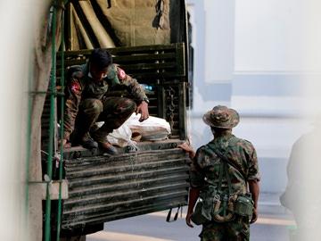 Soldados militares trasladan bolsas de un camión al Ayuntamiento de Yangon, en Birmania
