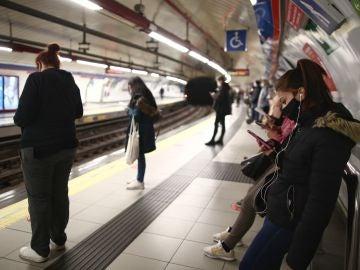 Varios pasajeros esperan en un andén de metro de la estación de Sol