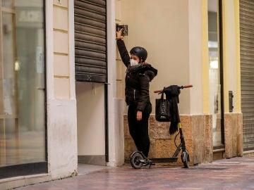 La trabajadora de un comercio cierra su establecimiento el primer día del cierre total de la hostelería y de tiendas a las 18.00h en Valencia