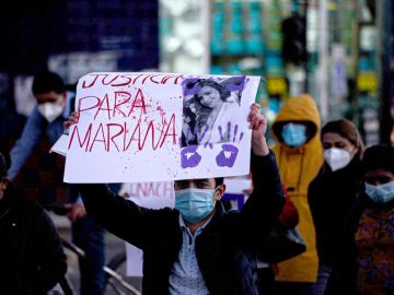 Un hombre sostiene un cartel de protesta durante una movilización para rechazar el feminicidio de una médica.