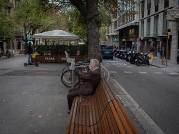 Un hombre descansa en un banco durante el cuarto día de la entrada en vigor de las nuevas restricciones en Cataluña