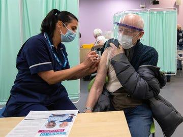 Una sanitaria vacuna a un hombre en Reino Unido