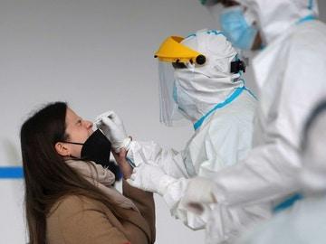 Un sanitario realiza una PCR a una mujer