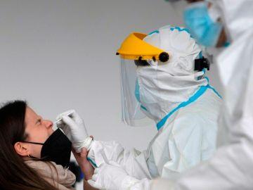 Un sanitario realiza una prueba PCR a una mujer.