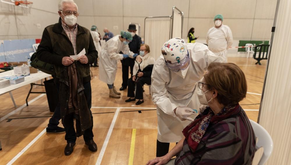 Una mujer recibe la primera dosis de la vacuna contra el coronavirus en un dispositivo instalado en un pabellón en Cartagena (Murcia)