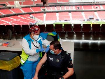 Un policía recibe la primera dosis durante el primer día de vacunación contra la covid-19 en el Wanda Metropolitano este jueves en Madrid