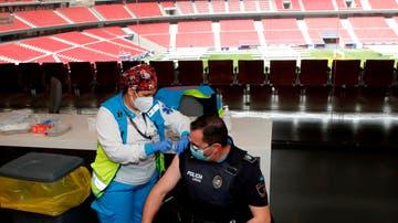 Un policía recibe la primera dosis durante el primer día de vacunación contra la covid-19 en el Wanda Metropolitano